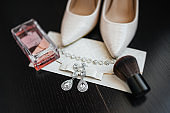 Wedding details. Atributes of young beautiful bride: brush, perfume, earrings, shoes, bracelet, letter with wedding invitation. Best day of live.