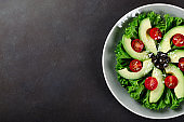 Sliced avocado with cherry tomatoes, olives, salad leaves and ch