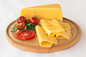 Cheese, tomato and green basil on a cutting board. White background