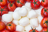 Mozzarella, red tomatoes with green tails closeup