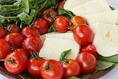 Suluguni cheese, tomatoes and ruccola closeup