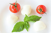 Mozzarella balls, basil  and tomato on a white background