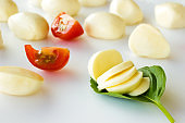 Sliced mozzarella on a green leaf, slices of tomato and mozzarella balls on a white background