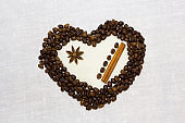 Coffee beans, star anise and cinnamon on a white background as the heart