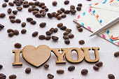 The words 'I love you', envelope, pen, spilled coffee on white background