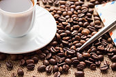 A cup of coffee, coffee beans, a letter and a pen on the table