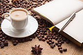 A cup of coffee, roasted grains, open notebook and pen on the table