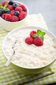 Oatmeal porridge in bowl with berries raspberries and blackberries.