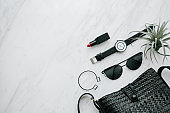 libstick with black sun glasses and bag and wristwatch and bracelet with shopping beauty concept for smart  and chic lady on marble background
