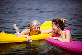 Senior mother and daughter swimming with inflatables in the sea