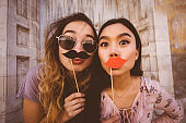 Women making faces with mustaches and lips on a stick