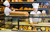 friendly mature bakers with fresh bread in bakery