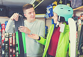 Seller is helping girl in equipment to choose ski