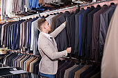 cheerful male customer examining men's suits