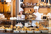 Bakery staff offering bread and different pastry