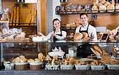 Portrait of charming  couple at bakery display with pastry