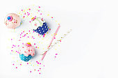 White background with party accessories. Invitation mockup. Confetti and muffins. cake. Flat lay