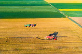 Combine harvester and tractor working in wheat field