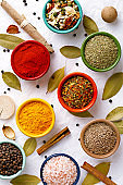 Spices in colorful bowls viewed from above. Various seasonings on a white background. Italian mix, cumin, chili pepper, curry powder, Himalayan salt, pepper, garlic, cinnamon, dried tomato. Top view