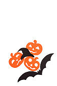 Silhouettes of orange pumpkins black hat and bat carved out of black paper are isolated on white