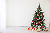 Christmas tree with red gifts in the white room Christmas