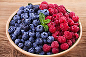 Blueberries and raspberries in clay bowl. Freshly picked berries on rustic background