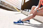 Girl suffering from ache in foot after jogging