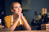 Pensive female barista situating in confectionary shop