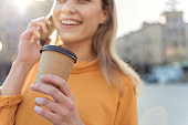 Carefree blond woman enjoying beverage during conversation