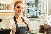 Joyful saleswoman working in confectionery