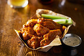 pile of tasty buffalo chicken wings in paper tray with celery
