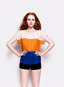 Slim redhead girl in stylish clothes Fashion model studio portrait