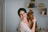Portrait of a beautiful bride on wedding day. The bride is kissing the dog.