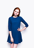 Young beautiful redhead woman in lovely blue dress