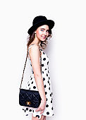Beautiful young girl in cute polka dots dress and hat
