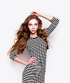 Beautiful young woman in lovely striped dress Fashion model studio portrait
