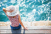 Woman with straw hat enjoying on sea pier