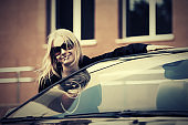 Happy young fashion woman in sunglasses next to her car