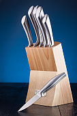 steel knifes in wooden block on the blue