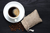 Hot aromatic coffee in a cup and a bag of coffee beans