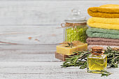 Natural cosmetic oil and natural handmade soap with rosemary on rustic wooden background.