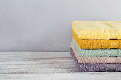 Stack of colorful bath towels on light background.