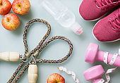 Dieting, healthy and active lifestyles Concept, sport shoes, tape measure, bottle of water, apples, jump rope and dumbbells top view flat lay background.