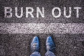Word burn out written on asphalt with legs and shoes, burn out concept