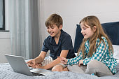 Small Boy And Girl Use Laptop Computer Sitting On Bed In Bedroom, Brother And Sister Surfing Internet