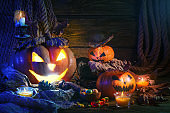 Halloween pumpkins and candy on wooden table at night