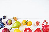 Top view of rainbow colored fruits over white background with copy space.