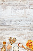 Wholegrain flour, oat flakes, olive oil, eggs in a carton tray, wooden spoon, grains and seeds over light wooden table.