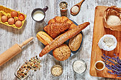 Set of fresh bread, wholegrain flour, eggs, grains and seeds, oat flakes, olive oil, milk, wooden board, spoon, rolling pin on a light rustic table.