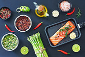 Top view of fresh salmon steak, green asparagus, dry brown rice and green peas, herbs, spices and olive oil over dark background.